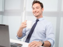 Smiling call center operator drinking tea