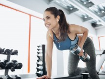 Young,Beautiful,Woman,Doing,Exercises,With,Dumbbell,In,Gym.,Glad
