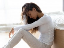 Unhappy,Woman,Touching,Hair,,Sitting,On,Floor,At,Home,,Thinking