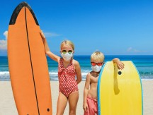 Young,Surfer,Kids,With,Surf,Boards,Wear,Protective,Mask,On