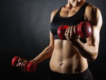 Torso,Of,A,Young,Fit,Woman,Lifting,Dumbbells,On,Dark