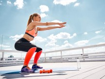 Sporty,Woman,Is,Doing,Squats,On,Roof,Top,Of,Urban
