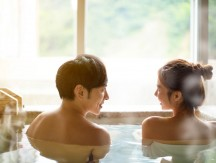 Rear,View,Young,Couple,Relaxing,In,Hot,Springs