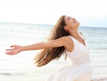 Woman,Relaxing,At,Beach,Enjoying,Summer,Freedom,With,Open,Arms
