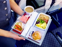 Midsection,Of,Stewardess,Holding,Tray,With,Airplane,Food