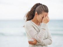Stressed,Young,Woman,In,Sweater,On,Beach,With,Cell,Phone