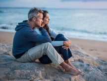 Beautiful,Couple,Sitting,On,A,Rock,At,The,Beach,Watching