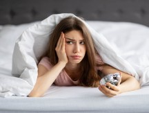 Unhappy,Young,Caucasian,Woman,Lying,In,Bed,With,Alarm,Clock,